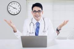 有时钟和膝上型计算机的医生在办公室 免版税图库摄影