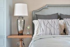 有时钟和经典华美的卧具的银色基本的台灯 免版税库存照片