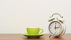 有时钟的咖啡杯在木桌上 库存图片