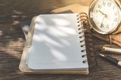 有时钟的空白的在古色古香的木背景的笔记本和笔 免版税库存照片