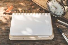 有时钟的空白的在古色古香的木背景的笔记本和笔 库存图片