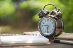有时钟的空白的在古色古香的木背景的笔记本和笔 库存照片