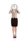 有时钟的美丽的白种人女商人在面孔。 免版税图库摄影