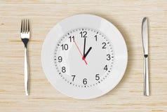 有时钟表盘的菜盘在木桌上 免版税库存照片