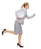 有时钟赛跑的镇静年轻女实业家 库存图片