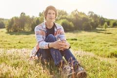 有时髦发型佩带的衬衣的英俊的人和牛仔裤坐草甸松弛和赞赏的阳光和fre绿草  免版税图库摄影