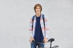 有时髦拿着背包的发型佩带的衬衣和牛仔裤的年轻骑自行车者站立在去他的自行车附近有横跨c的步行 库存图片