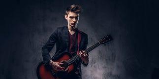 有时髦的头发的时髦的年轻音乐家在典雅的衣裳,使用在一把声学吉他 免版税图库摄影
