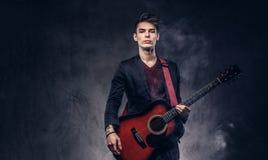 有时髦的头发的时髦的年轻音乐家在典雅的衣裳,使用在一把声学吉他 免版税库存图片