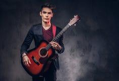 有时髦的头发的时髦的年轻音乐家在典雅的衣裳,使用在一把声学吉他 库存图片