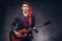 有时髦的头发的时髦的年轻音乐家在典雅的衣裳,使用在一把声学吉他 免版税库存照片