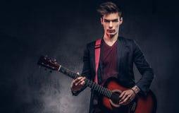 有时髦的头发的时髦的年轻音乐家在典雅的衣裳,使用在一把声学吉他 库存照片