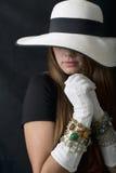 有时髦的懒散的帽子、长的葡萄酒白色手套和首饰的美丽的少妇 免版税图库摄影