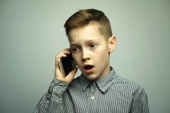有时髦的理发的少年严肃的男孩谈话在智能手机 库存图片