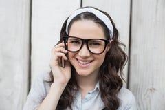 戴有时髦的眼镜的微笑的时髦妇女电话 库存照片