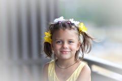 有时兴的发型的一点微笑的迷人的女孩,站立在阳台 免版税库存照片