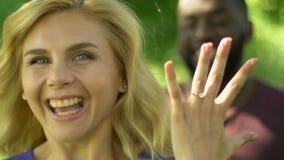 有昂贵的定婚戒指的愉快的白肤金发的妇女陈列手,提出提案 股票录像