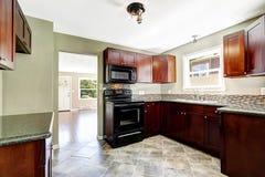 有明亮的伯根地内阁和黑装置的厨房 库存照片