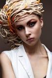 有明亮的创造性的构成的一个女孩 与一个草帽的美好的模型在她的头 纯净的光亮的皮肤 面孔的秀丽 库存照片
