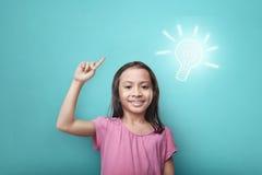 有明亮的想法标志的聪明的亚裔孩子在她的头上 免版税库存图片
