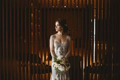 有明亮的构成和婚礼发型的美丽和肉欲的深色的式样女孩,在有花束的o时兴的白色鞋带礼服 库存图片