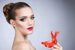 有明亮的构成和红色花的妇女 库存照片