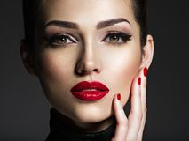 有明亮的构成和红色钉子的美丽的妇女 免版税库存图片