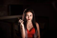 有明亮的构成和长的头发的妇女在她的手上的拿着一个电话 库存照片