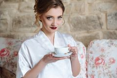 有明亮的构成的一个美丽的女孩食用早餐并且喝她的早晨咖啡 与灰色蓝色眼睛的一个模型 免版税库存照片