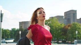 有明亮的构成的华美的白肤金发的妇女走在城市街道上的阳光下的 股票视频