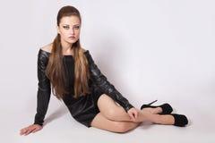 有明亮的构成的少妇在一双黑暗的礼服和黑鞋子 库存照片