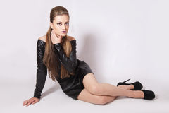有明亮的构成的少妇在一双黑暗的礼服和黑鞋子 免版税库存照片