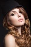 有明亮的构成的美丽的在帽子的女孩和卷毛 秀丽表面 免版税库存照片
