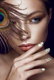 有明亮的构成的美丽的女孩,修指甲设计和孔雀在她的面孔用羽毛装饰 艺术钉子 库存照片
