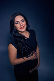 有明亮的构成的美丽的孕妇,长的黑发,在摆在照片演播室的黑配件礼服 库存照片