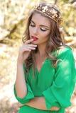 有明亮的构成的美丽的性感的女孩女王/王后在有一个冠的一件长的礼服在他的顶头busick在明亮的晴朗的s的森林里走 免版税图库摄影
