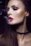 有明亮的构成的美丽的性感的深色的女孩,红色嘴唇,从嘴的烟 秀丽表面 免版税图库摄影