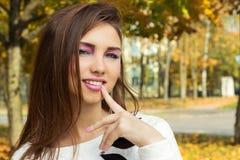 有明亮的构成的美丽的愉快的微笑的女孩在与肥满嘴唇的岩石样式有对她的嘴的一个手指的在公园温暖的秋天 免版税库存照片