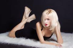 有明亮的构成红色嘴唇的美丽的性感的典雅的醒目的白肤金发的妇女在一件黑礼服在白色毛皮说谎在演播室 免版税库存照片