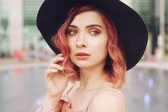 有明亮的桃红色卷发和一个黑海滩帽子的一个女孩在喷泉的背景站立 有美丽的一个女孩轻拍 免版税库存照片