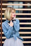有明亮的桃红色嘴唇和短的金发的朝她的左边看听到在a的音乐的一个梦想的女孩的一张接近的画象 免版税图库摄影