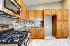 有明亮的棕色内阁的豪华厨房室和马赛克围住t 免版税库存图片