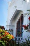 有明亮的橙色开花的树的圣保罗` s主教制度的教会在一个夏日在基韦斯特岛,佛罗里达 库存照片