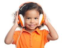 有明亮的橙色耳机的小美国黑人的女孩 免版税库存照片