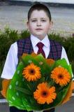 有明亮的橙色花花束的美丽的学校学生  库存图片