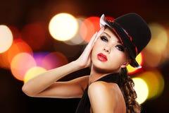 有明亮的红色嘴唇和时兴的帽子的性感的妇女 库存图片