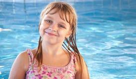 有明亮的蓝色池的微笑的小女孩浇灌 免版税图库摄影
