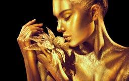 有明亮的金黄闪闪发光的时装模特儿妇女在摆在的皮肤,幻想花 美女画象有发光的构成的 库存图片