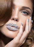 有明亮的水晶的钉子、嘴唇,长的睫毛和卷毛的美丽的女孩 秀丽表面 免版税库存图片