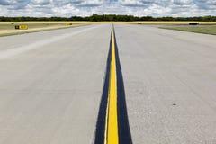 有明亮的黄线和金黄Wheatfield的农村机场跑道 图库摄影
